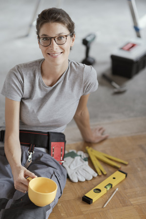 Young smiling woman having a coffee break and sitting on the floor, she is doing a home renovation