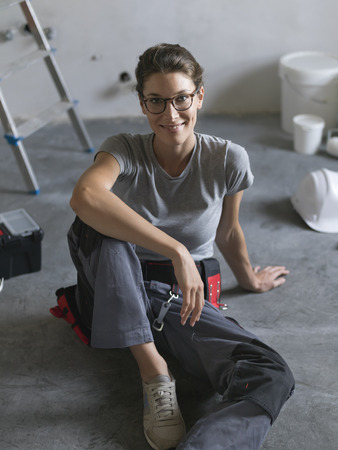 Professional repairwoman doing a home renovation, she is sitting on the floor and smiling at camera