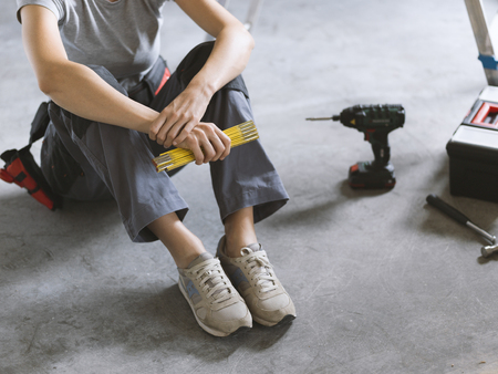 Woman sitting on the floor with tools and holding a folding ruler, she is planning a home renovation Stock Photo - 108157952