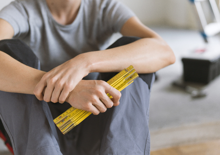 Woman sitting on the floor with tools and holding a folding ruler, she is planning a home renovation Stock Photo
