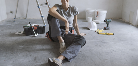 Woman sitting on the floor with tools, she is planning a home renovation Stock Photo