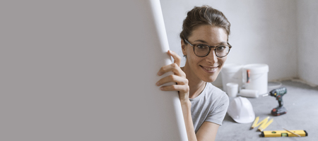 Happy woman renovating her new house and checking a project, she is smiling at camera
