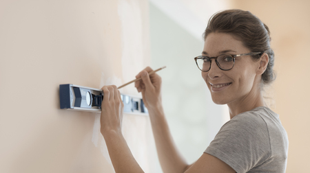 Young smiling woman working with a spirit level and drawing on a wall, home renovation and construction concept