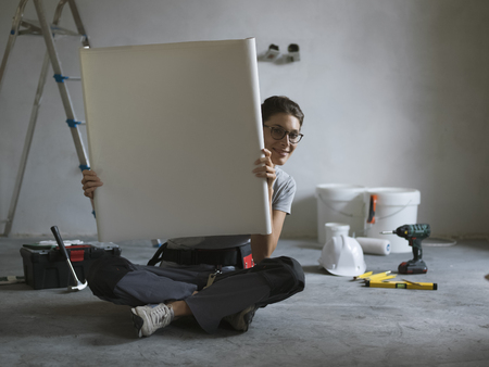 Happy woman renovating her new house and checking a project, she is smiling at camera and sitting on the floor Stock Photo