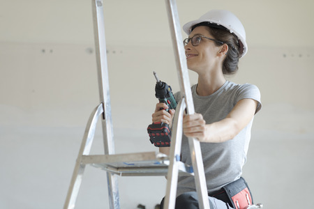 Young smiling woman using a drill, home renovation and DIY concept