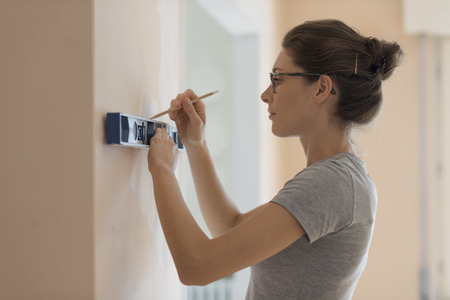Young woman working with a spirit level and drawing on a wall, home renovation and construction concept