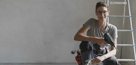 Professionelle Reparaturfrau mit Werkzeuggürtel, die eine Hausrenovierung durchführt, sie posiert und hält einen Bohrer