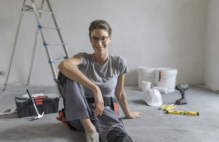 Attractive smiling woman renovating her house, she is sitting on the floor with tools and posing, home makeover concept