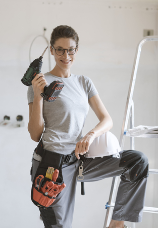 Professional repairwoman with tool belt and safety helmet doing a home renovation, she is posing and holding a drill