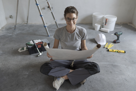 Woman renovating her home and sitting on the floor with tools and paint buckets, she is checking the house plan and making a new project Stock Photo