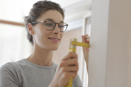 Smiling young woman doing a home makeover, she is measuring a wall using a folding ruler, DIY and house renovation concept Stock Photo