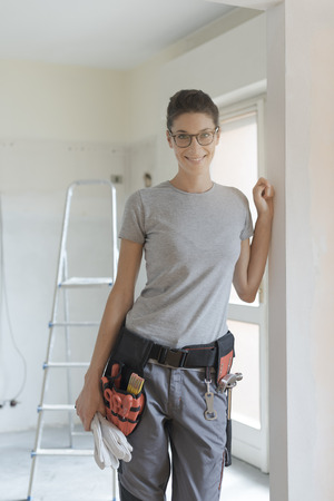 Confident female contractor posing with tool belt and smiling at camera, female professionals concept
