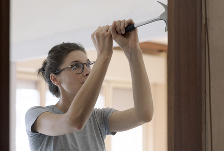 Woman repairing a door at home using a hammer: home renovation and DIY concept Stock Photo