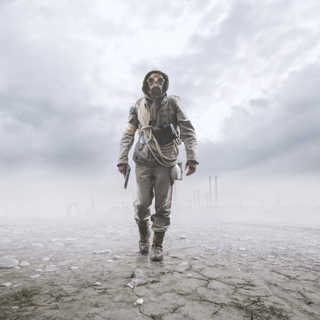 Brave soldier with gas mask and gun walking in a polluted post atomic landscape with toxic smog and clouds: environmental disaster and apocalypse concept Stock Photo