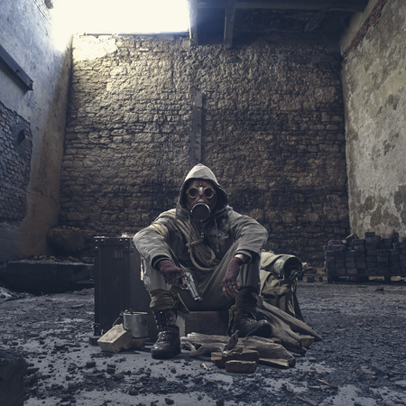 Nuclear disaster survivor in a post apocalyptic setting, he is wearing a gas mask and holding a gun: environmental disaster and chemical warfare concept