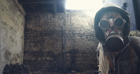 Nuclear disaster survivor in a post apocalyptic setting, he is wearing a gas mask and walking in a destroyed city Stock Photo