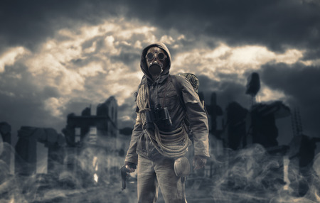 Post apocalyptic survivor standing with a gas mask and a gun, destroyed city and toxic smog in the background: environmental disaster and armageddon concept