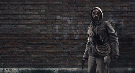 Coraggioso sopravvissuto post apocalittico con maschera antigas e pistola: disastro ambientale, criminalità e concetto di guerra chimica