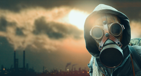 Brave post apocalyptic survivor wearing a gas mask; polluting industries, toxic smog and environmental degradation in the background
