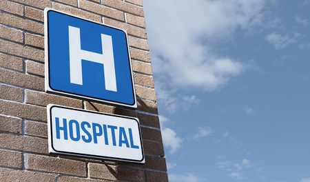 Hospital road sign hanging on a building wall: medical services and departments concept