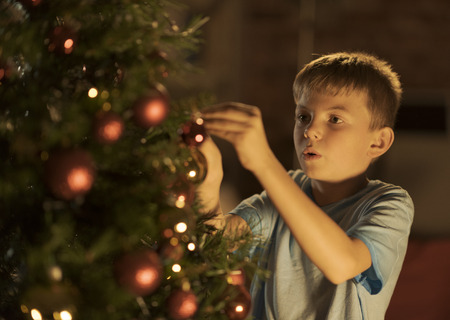Cheerful boy decorating his Christmas tree with red baubles: holidays and childhood concept