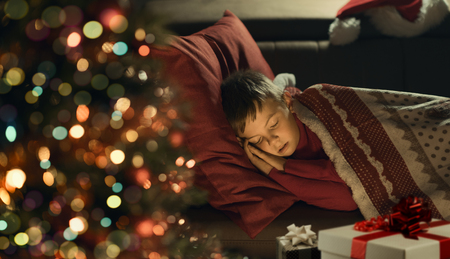Cute little boy sleeping on the sofa next to the Christmas tree, he is waiting for Santa Claus, Christmas and holidays concept Archivio Fotografico