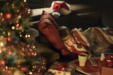 Cute little boy sleeping on the sofa next to the Christmas tree, he is waiting for Santa Claus, Christmas and holidays concept Stock Photo
