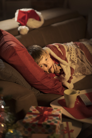 Cute boy lying on the sofa at home and waiting for Santa on Christmas Eve: childhood and holidays concept Standard-Bild - 116701619