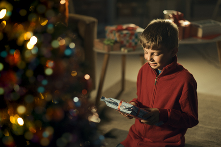 Happy boy celebrating Christmas at home, he is smiling and holding a gift, Christmas tree in the foreground Standard-Bild - 116701672