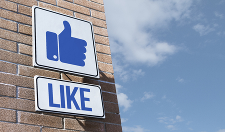 Thumbs up icon on a road sign in the city street: like and social media concept Stock Photo