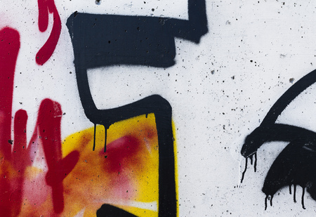 Colorful graffiti art on a wall with spray paint drips close up