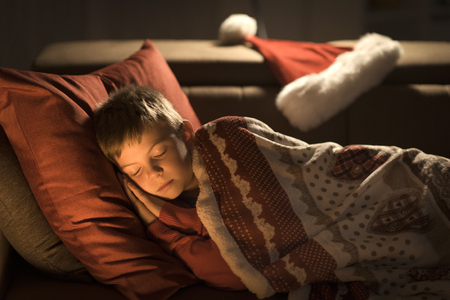 Cute little boy sleeping on the sofa on Christmas Eve, Santa Claus left his hat next to him Stock Photo