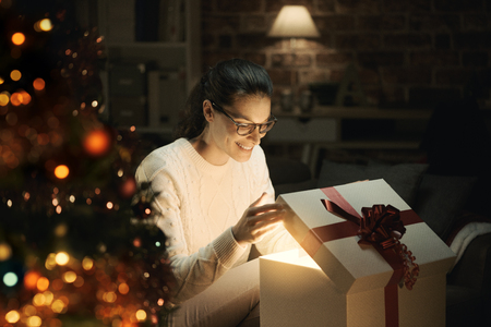 Happy woman opening a magical shiny Christmas gift at home, Christmas tree in the foreground Stock Photo
