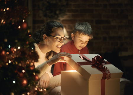 Happy boy and his mother opening a magical Christmas gift at home, Christmas tree in the foreground: holidays and family concept