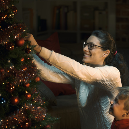 Happy mother and son decorating their Christmas tree together, they are hanging shiny baubles: holidays and family concept Stock Photo