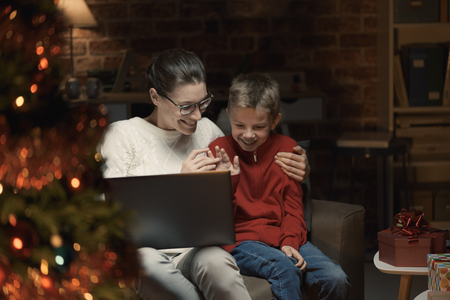 Happy mother and boy connecting with their laptop and having a video call, they are waving and sending Christmas wishes to their friends