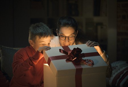 Cheerful boy and his mom opening an amazing Christmas gift with a surprise inside, holidays and family concept