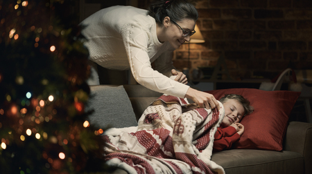 Caring loving mother tucking her child in, he is napping on the sofa on Christmas eve Stock Photo