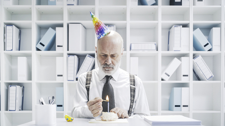Senior businessman having a sad lonely birthday in the office, he is wearing a party hat and having a small cake alone