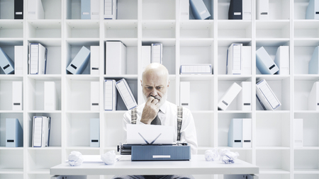 Senior businessman or journalist working in the office, he is sitting at desk and using a typewriter Stock Photo