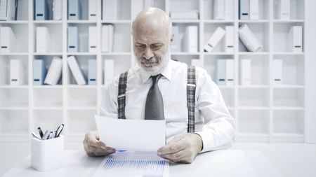 Professional senior businessman working in the office, he is checking paperwork and financial reports Stock Photo