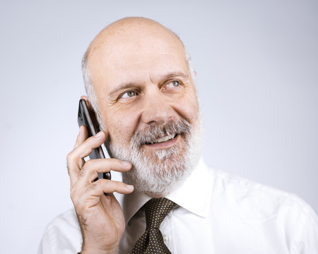 Happy mature man calling with his smartphone and smiling