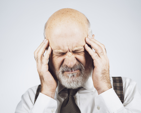 Senior man having a bad headache, he is suffering and feeling confused
