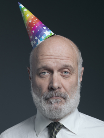 Funny senior bald man wearing a colorful party hat: he is lonely, sad and disappointed Stock Photo