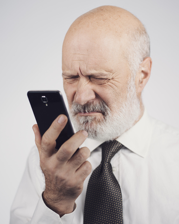 Senior man using apps on the smartphone, he is having difficulties and vision problems Stock Photo