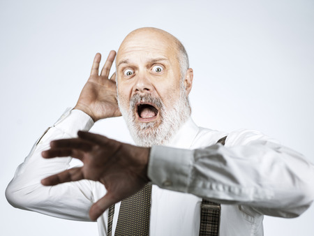 Terrified panicked senior man shouting out loud with hands raised Stock Photo