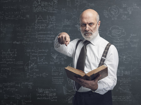 Senior academic professor holding a book and pointing at camera: exams and traditional education concept Stock Photo