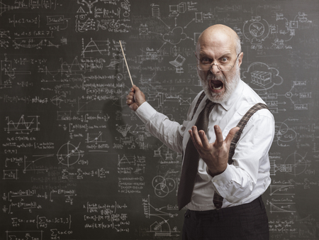 Senior authoritarian professor yelling and pointing at the blackboard with a stick: traditional education concept Standard-Bild - 116681606