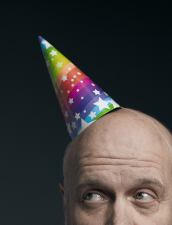 Funny senior bald man wearing a colorful party hat and looking up, close up Standard-Bild - 116681608