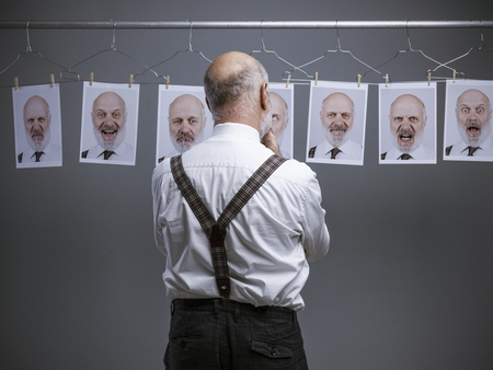 Mature businessman staring at his multiple personalities and expressions on a collection of hanging portraits: mind self analysis and emotions concept Standard-Bild - 116681614
